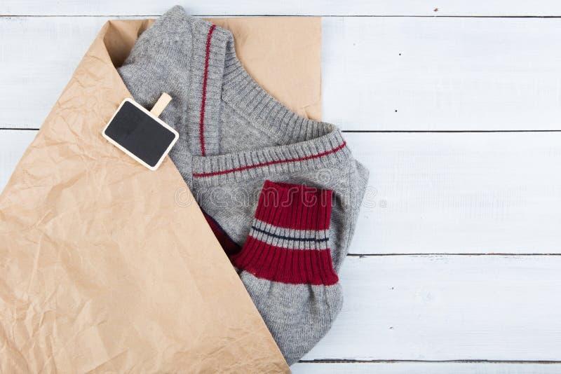 Shoppa för gåvor - varm tröja i pappers- en påse- och försäljningssignbo fotografering för bildbyråer