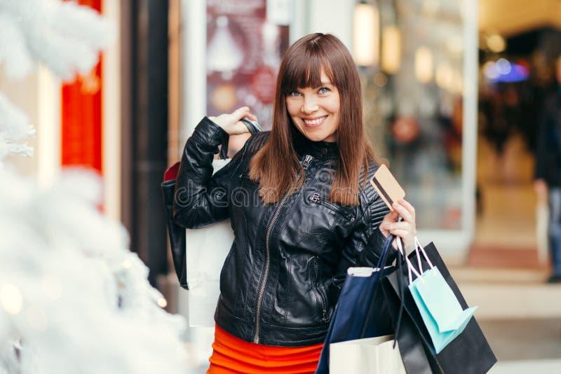 shoppa för jul Härlig lycklig womanl med kreditkorten i S royaltyfri fotografi