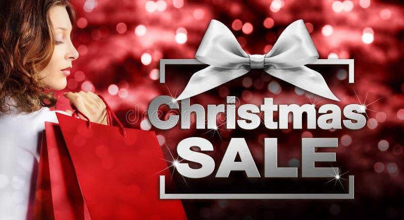 Shoppa för jul, kvinna med påsen och försäljningstext i askram på arkivfoton