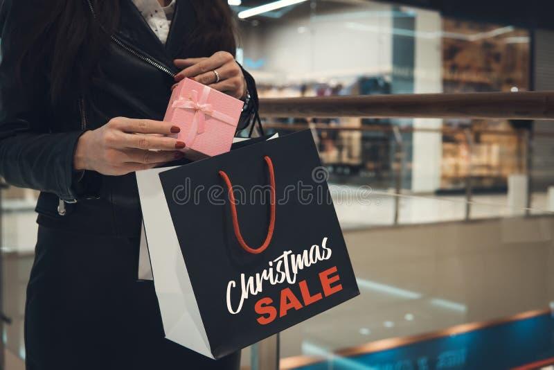 shoppa för jul Lycklig kvinna med shoppingpåsar i shoppinggalleria försäljningar white för julgåvaisolering hissar, exponeringsgl royaltyfria bilder