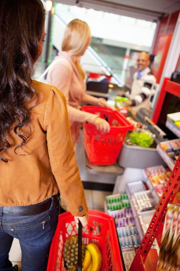 shoppa för kunder för korg bärande royaltyfri bild