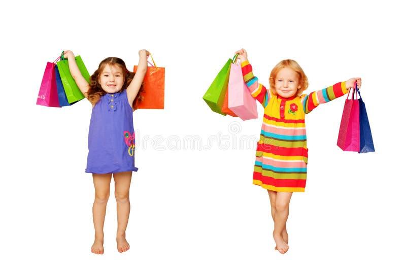 Shoppa för ungar. Två liten flicka med deras köp och gåvor. arkivbild