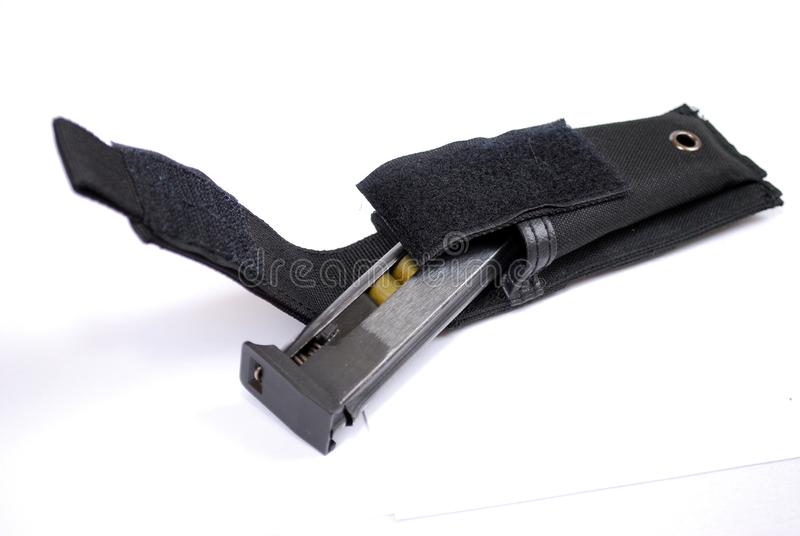 Shoppa hållaren som laddas med kassetter från ett vapen i en svart tygkassettpåse på en vit bakgrund royaltyfri foto