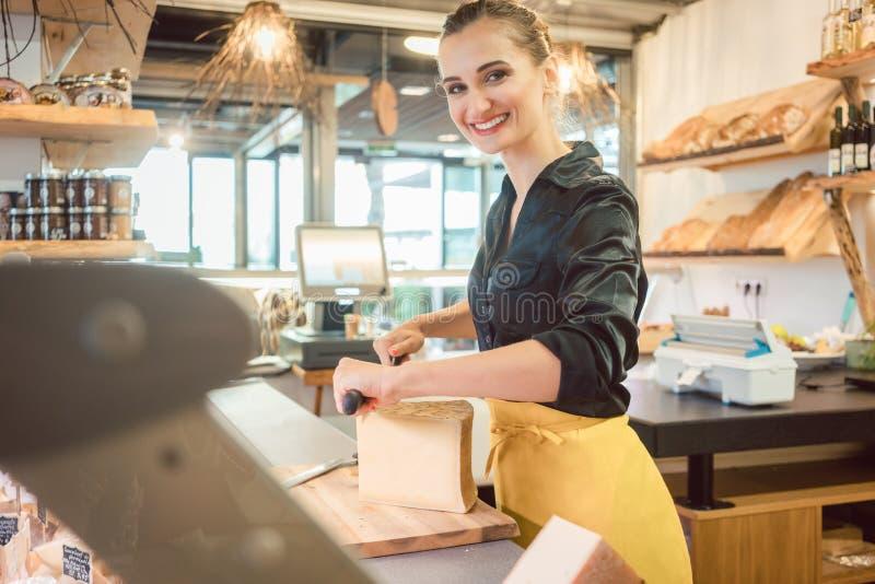 Shoppa kontoristen i delikatessaffär som klipper ost royaltyfria bilder
