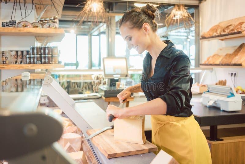 Shoppa kontoristen i delikatessaff?r som klipper ost arkivfoton