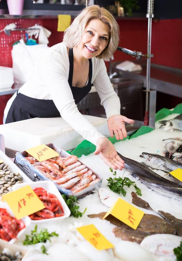 Shoppa kvinnligt sälja för material som kylas på isfisk i supermarket arkivfoto