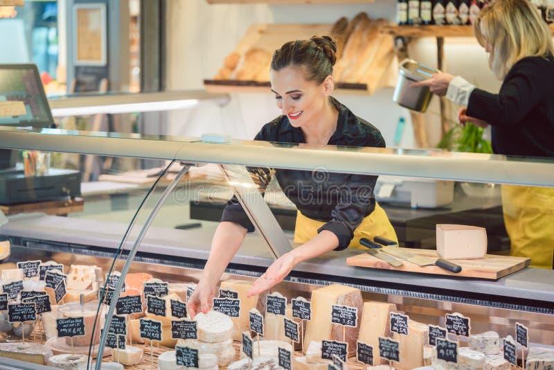 Shoppa ost för kontoristkvinnasortering i supermarketskärmen royaltyfri bild