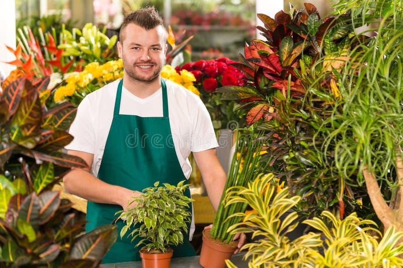 Shoppar arbeta i trädgården för blomma för lycklig male blomsterhandlare funktionsdugligt arkivbild