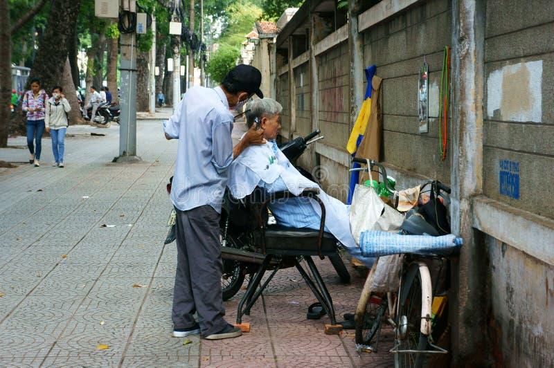 Shoppar barberaren för öppen luft för vietnames på trottoar arkivbilder