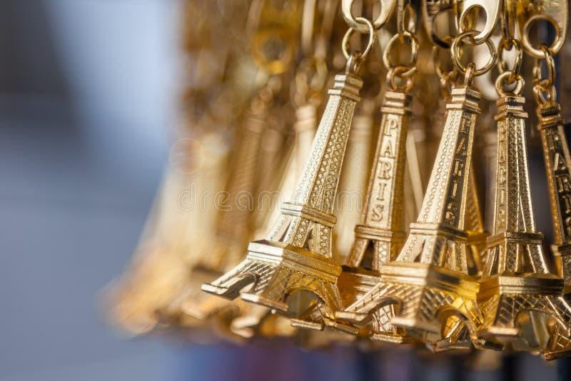 Shoppar den nyckel- kedjan för den lilla guld- Eiffeltorn i en souvenir fotografering för bildbyråer