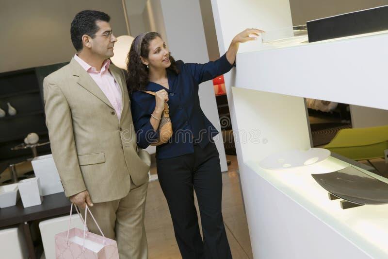 Shoppar den undersökande Glass bunken för par i möblemang royaltyfria foton