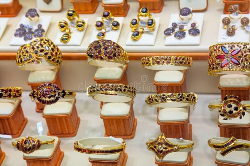 Shoppar guld- smycken för lyxig granatrött fönsterskärm arkivbilder
