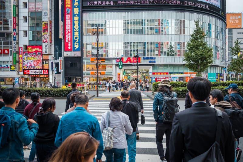Shoppar och fullsatt folk på den Shinjuku staden i Tokyo fotografering för bildbyråer