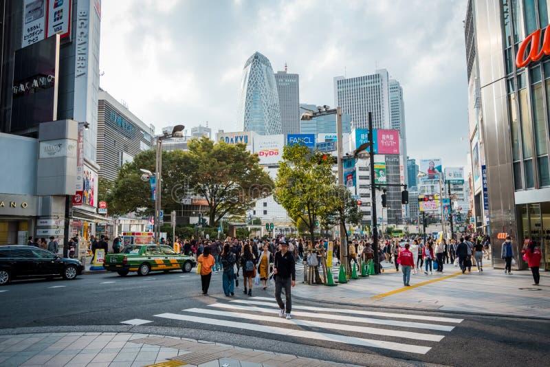 Shoppar och fullsatt folk på den Shinjuku staden i Tokyo arkivfoton