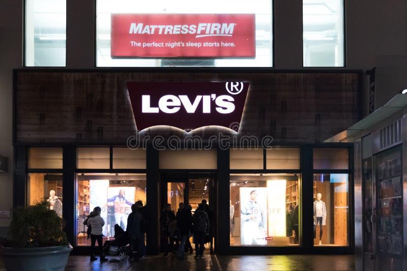 Shoppare går förbi ett lager för kläder för detaljhandel för Levi ` s i New York City, Levi Strauss, & Co är en privat rymd ameri arkivfoton