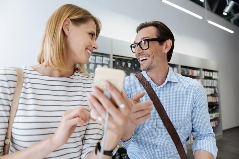 Shoppare som får upphetsade på elektroniklagerskärm royaltyfri bild