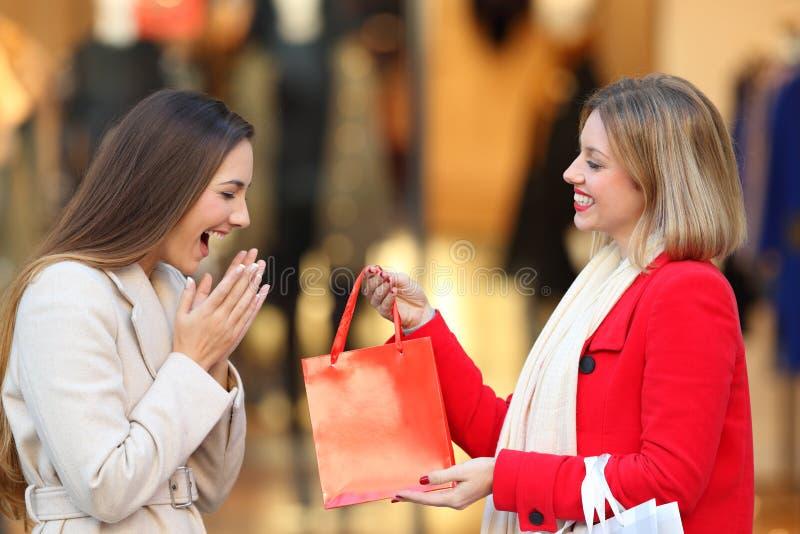 Shoppare som ger en gåva till en vän i vinter fotografering för bildbyråer