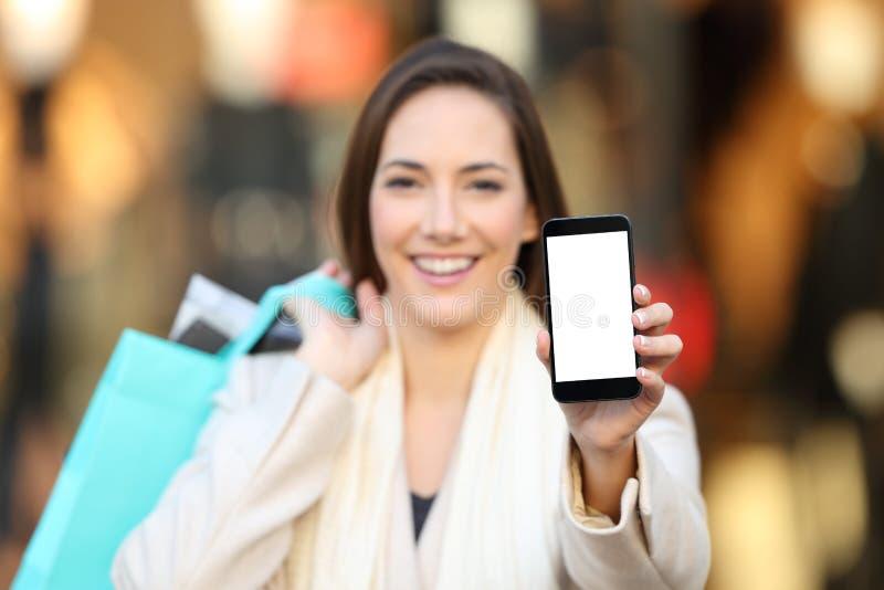 Shoppare som visar en tom telefonskärmåtlöje upp utomhus royaltyfri fotografi