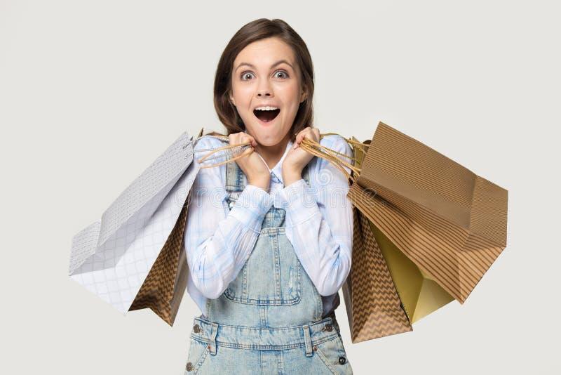Shoppareflicka som rymmer högar av shoppingpåsar som isoleras på grå färger arkivfoton