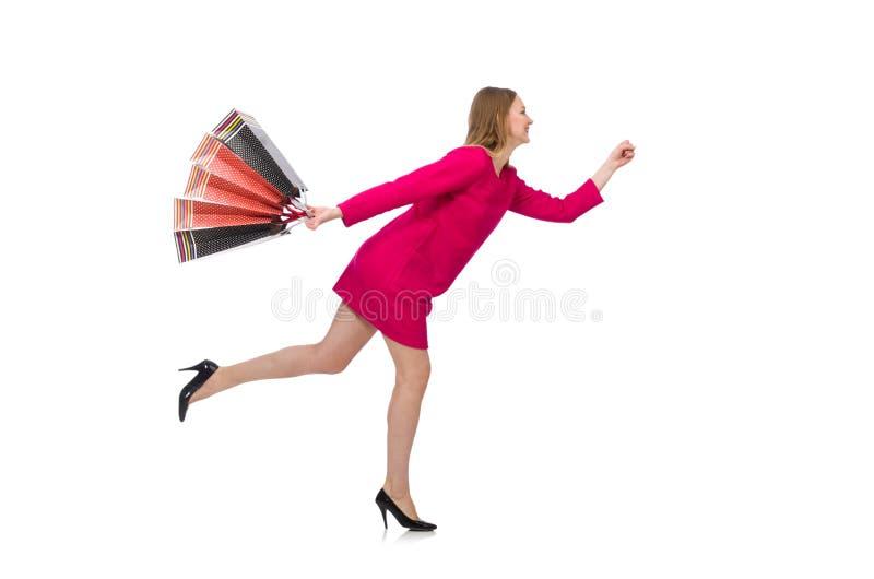 Shoppareflickan i rosa färger klär hållande plastpåsar som isoleras på whit fotografering för bildbyråer