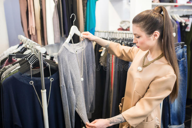 Shopparekvinna som väljer kläder fotografering för bildbyråer