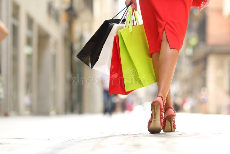 Shopparekvinnaben som går med shoppingpåsar royaltyfria bilder