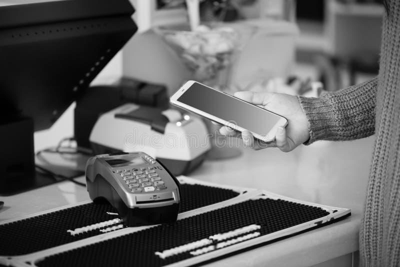 Shopparen gör betalning genom att använda smartphonen NFC-teknologi i folkliv royaltyfri bild