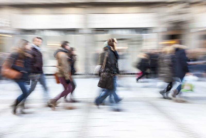 Shopparen som går av, shoppar framme fönstret arkivfoton