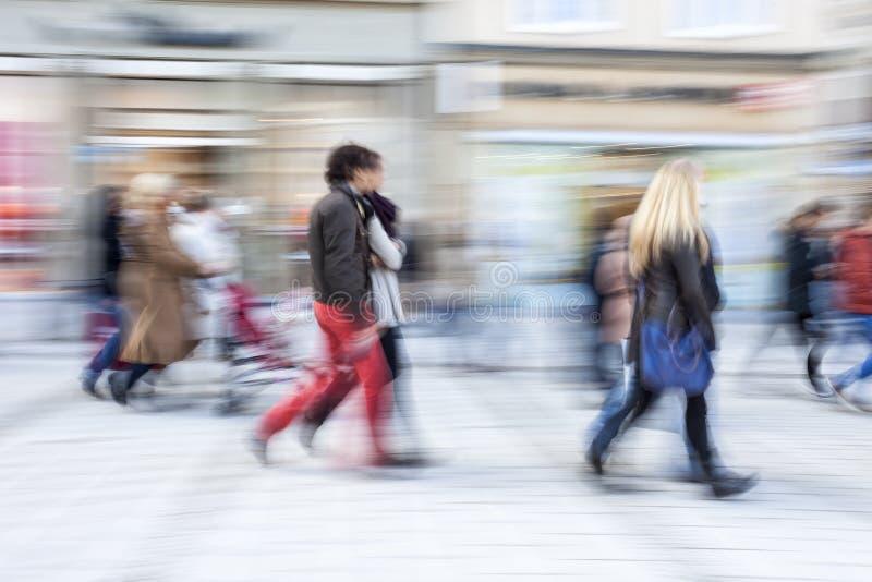 Shopparen som går av, shoppar framme fönstret arkivfoto