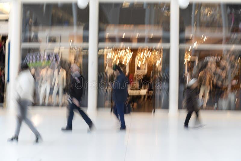 Shopparen som går av, shoppar framme fönstret på skymning royaltyfri fotografi