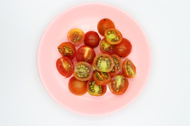 Shopped tomatoes in pink dish on white background. High resolution image gallery royalty free stock images