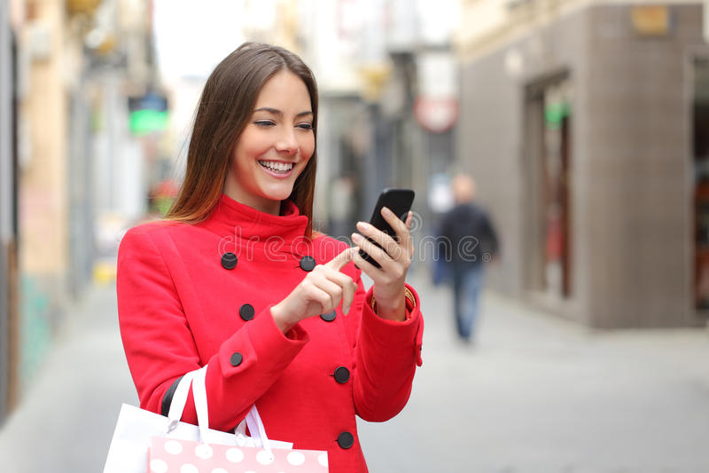 Shopper buying online on the smart phone. Shopper woman buying online on the smart phone in the street
