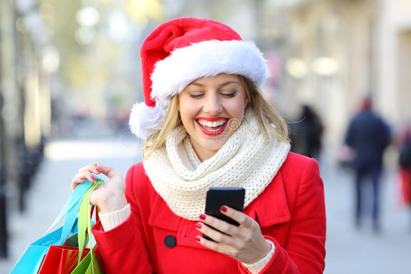 Shopper checking phone on christmas in the street. Front view portrait of a happy shopper holding shopping bags checking phone on christmas in the street stock photography