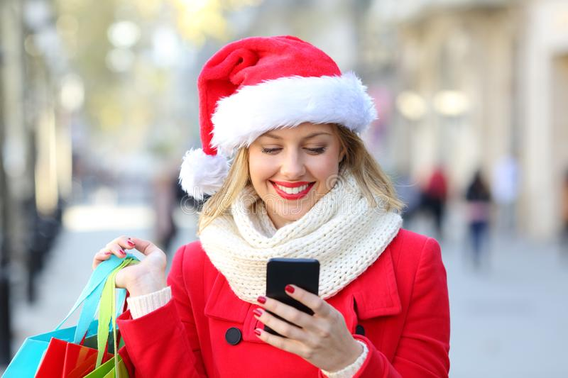Shopper checking phone content on christmas. Happy shopper checking phone content on christmas in the street royalty free stock photo