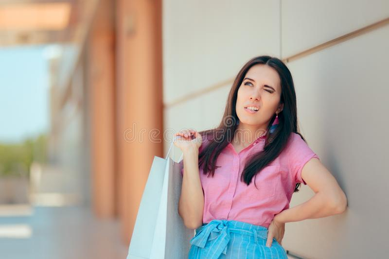 Tired Woman After Shopping Session at the Mall. Shopper girl in pain feeling her spine injured after carrying many bags royalty free stock photo
