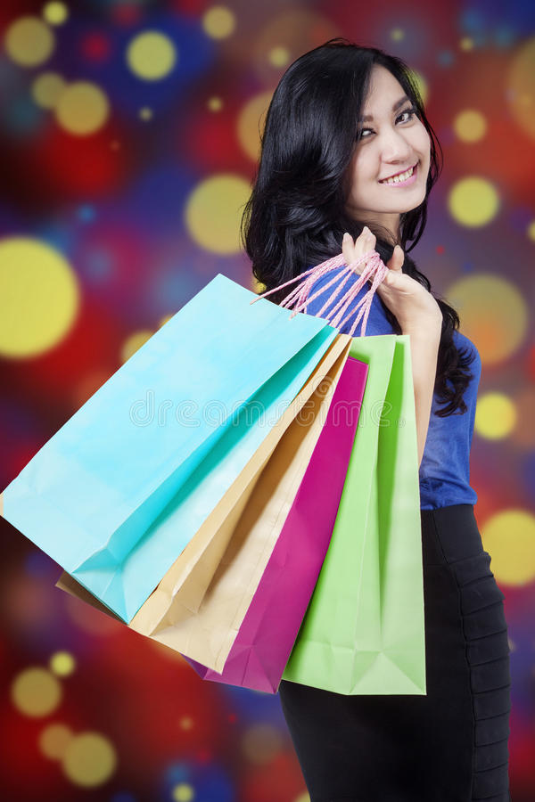 Shopper holds shopping bags with defocused background royalty free stock images