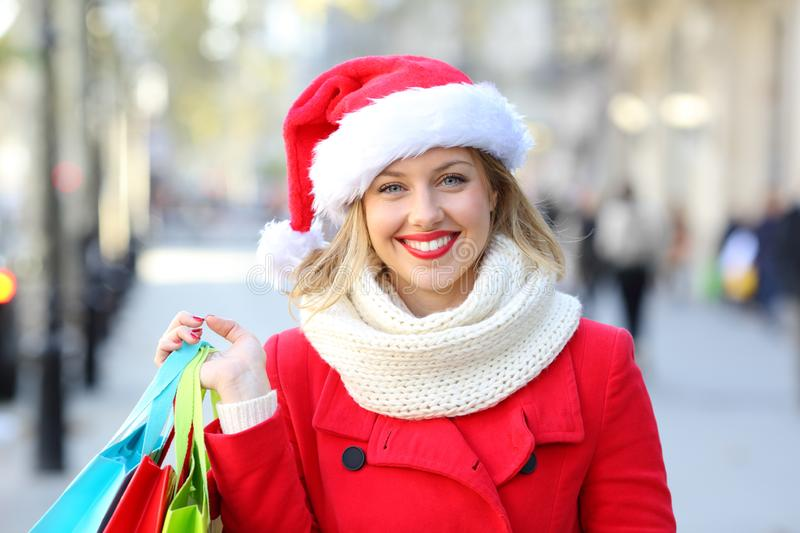 Shopper looking at you on christmas in the street. Front view portrait of a happy shopper looking at you on christmas in the street royalty free stock photo