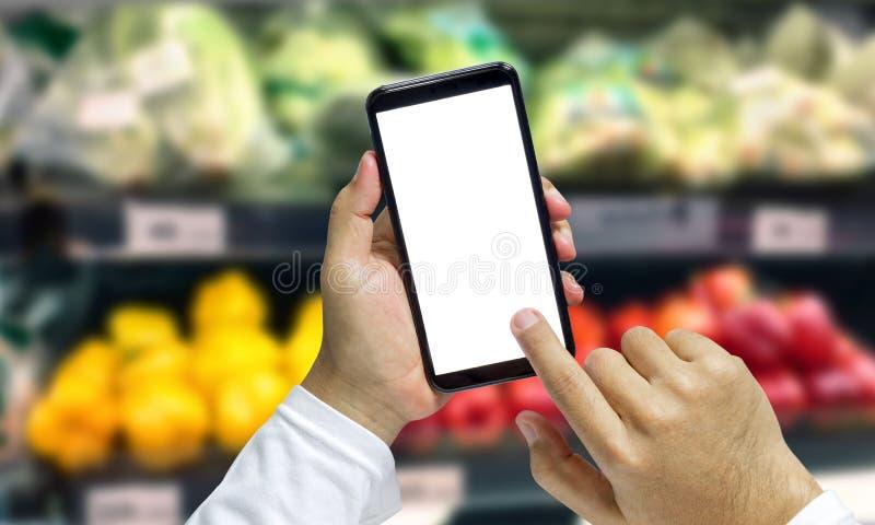 Shopper Mobile Smart Phone in de hand, bekijk meer details en vergelijk de prijzen in supermarkten stock afbeeldingen