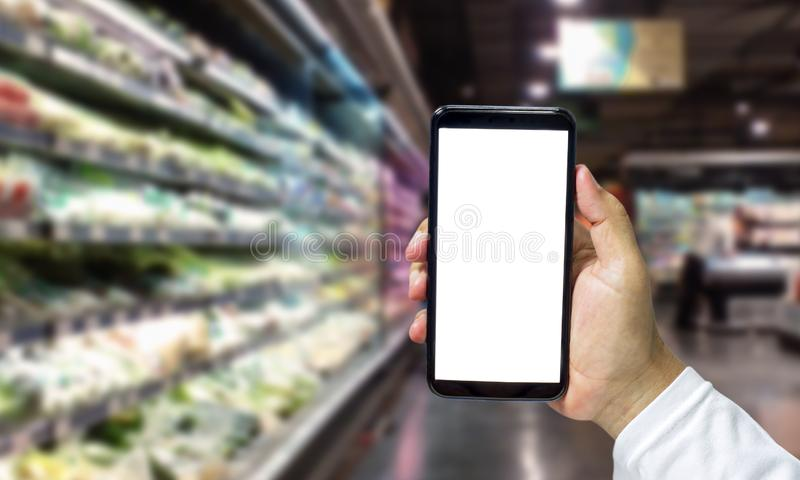 Shopper Mobile smart phone in hand, and see more detail and compare the prices in supermarkets.  stock image
