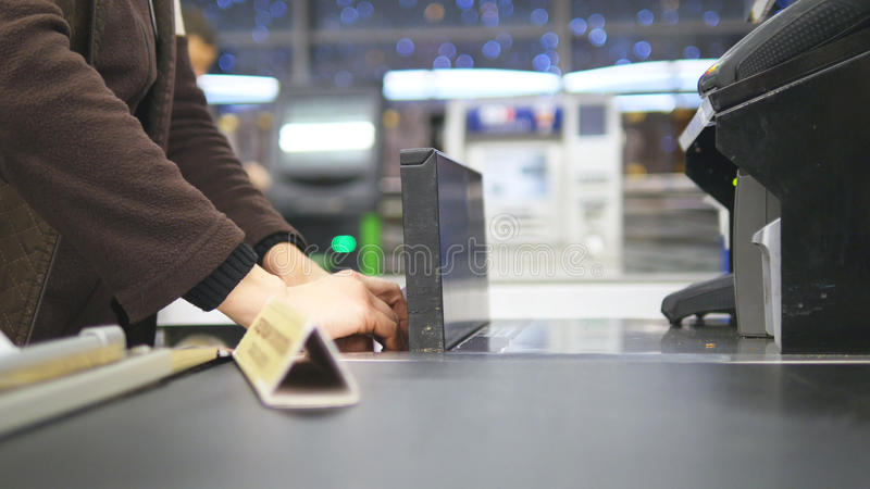 Shopper paying for products at checkout. Foods on conveyor belt at the supermarket. Cash desk with cashier and terminal stock photos