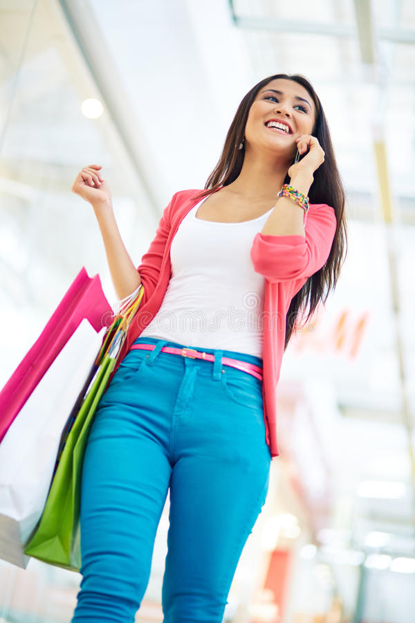 Shopper phoning. Vertical shot of a happy girl with purchases speaking by the phone royalty free stock photography
