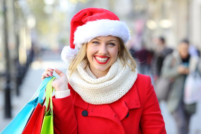 Shopper posing in the street on chritmas holidays. Front view portrait of a happy shopper holding shopping bags posing in the street on chritmas holidays royalty free stock photos