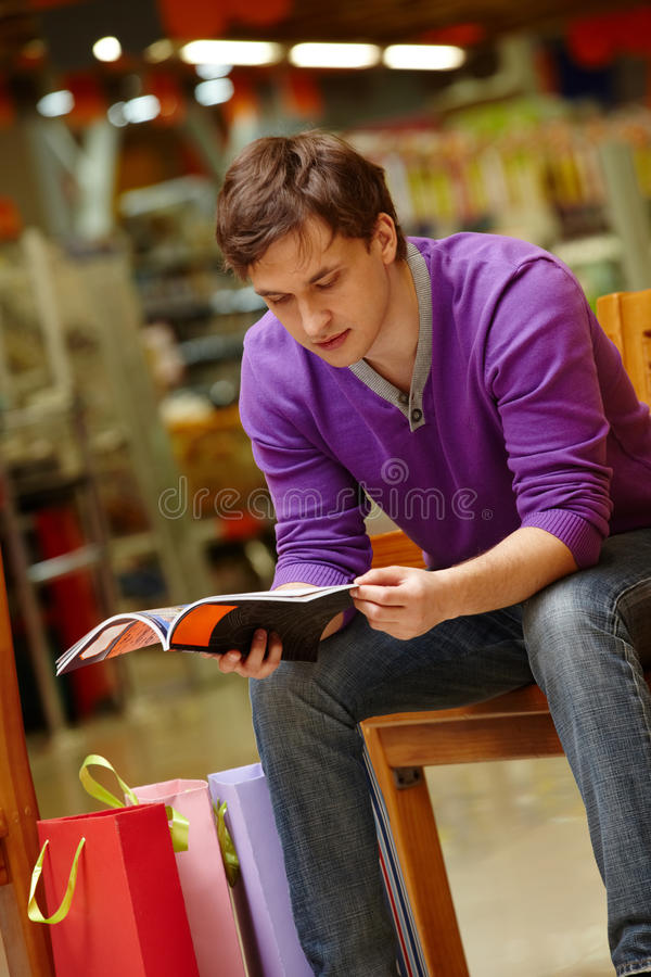 Shopper reading. Portrait of shopper looking through magazine with paperbags near by royalty free stock photos