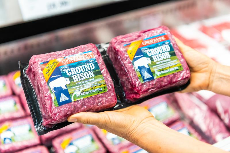 Shopper`s hand holding a package of Great Range Brand ground bison meat. In a supermarket aisle royalty free stock photo
