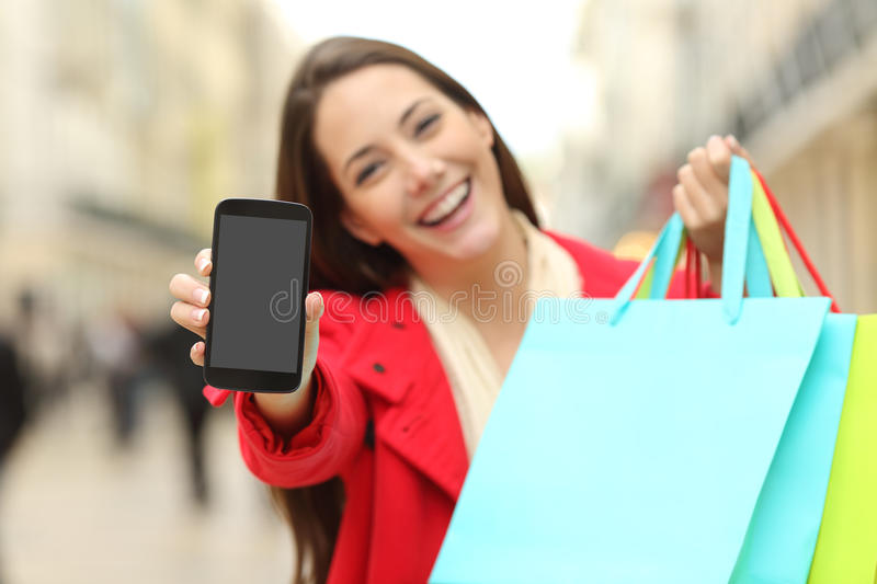 Shopper with shopping bags showing phone. Front view of a shopper holding blank shopping bags showing to the camera a smart phone screen with an urban background royalty free stock images