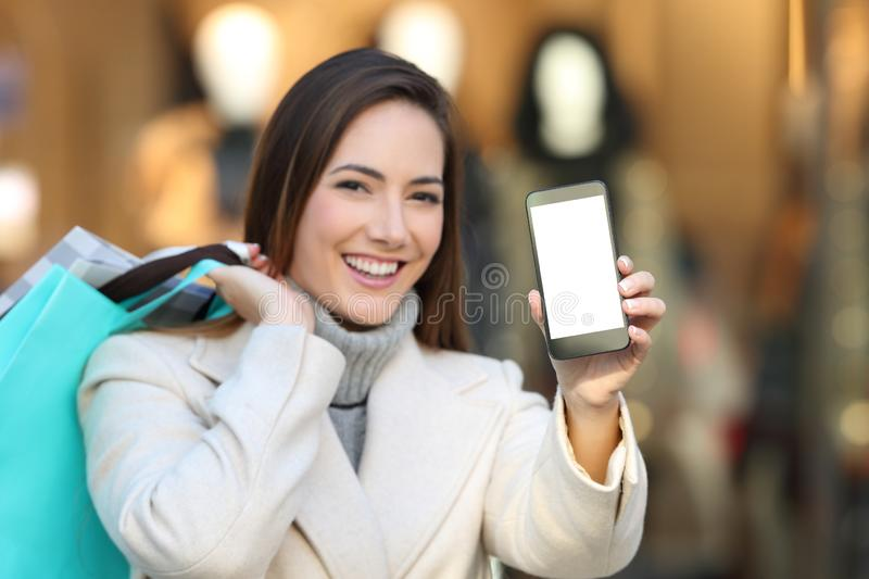 Shopper showing blank phone screen in winter. Happy shopper holding shopping bags showing blank smart phone screen in winter in a mall stock photography