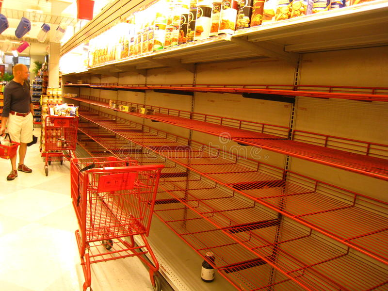 Shopper staring at empty shelves in NY grocery. As Hurricane Irene approached on 8/27/11, New York city supermarket shelves emptied out of essential non stock images