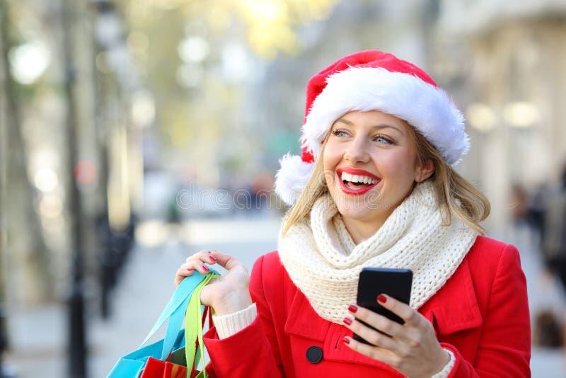 Shopper thinking holding a phone on christmas. Happy shopper holding a phone and shopping bags thinking looking at side on christmas in the street stock photo