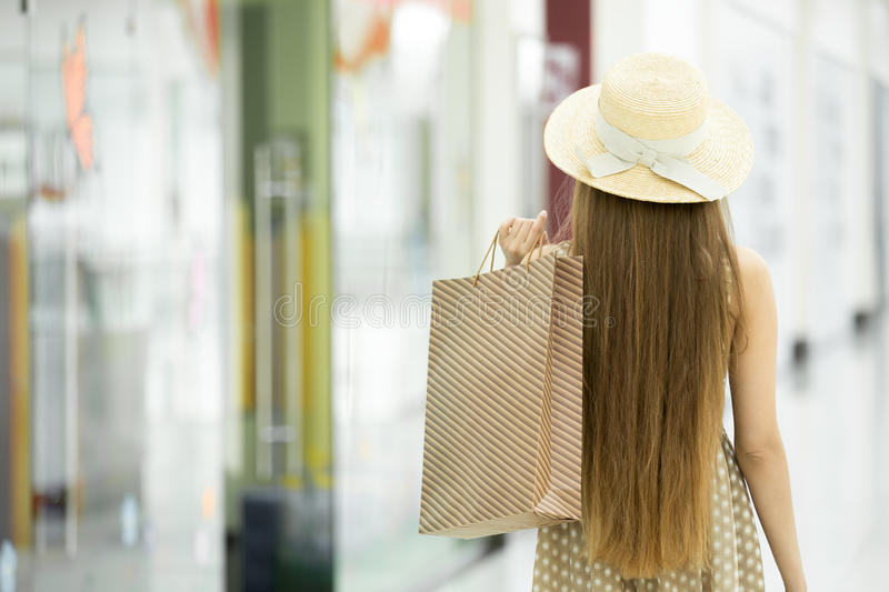 Shopper woman in shopping centre. Back view. Young pretty woman wearing hat and holding shopping paper bag over shoulder walking away over blurred shopping royalty free stock photography