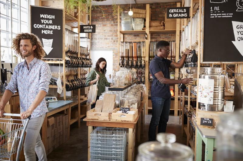 Shoppers In Dried Goods Section Of Sustainable Plastic Free Grocery Store royalty free stock images
